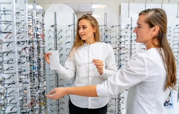 Счастливый клиент-женщина или оптик стоит с необработанными очками на заднем плане в оптическом магазине