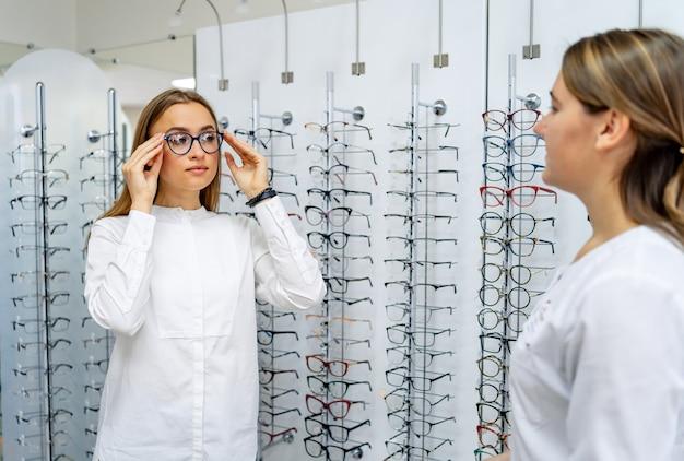 幸せな女性のクライアントまたは眼鏡技師は、光学店で眼鏡をかけて立っています。