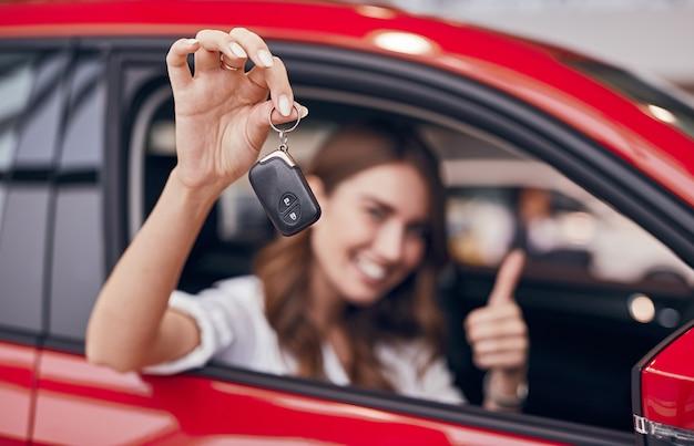 새 차량에 앉아 쇼룸에서 키를 시연하는 동안 웃고 엄지 손가락을 몸짓으로 보여주는 행복한 여성 고객
