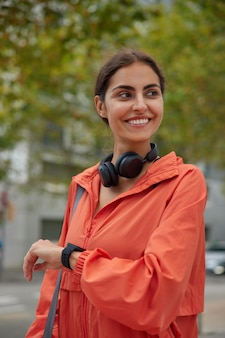 Happy female coach or fitness instructor waits for training to begin checks smartwatch during workout poses with sport facilities walks in park looks away. exercising and electronics concept