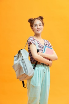 Happy female college student on yellow background