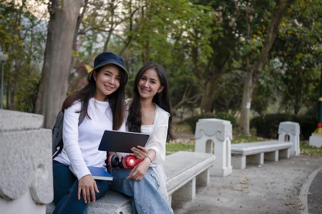 Счастливые студентки колледжа используют цифровой планшет и сидят вместе на скамейке в кампусе