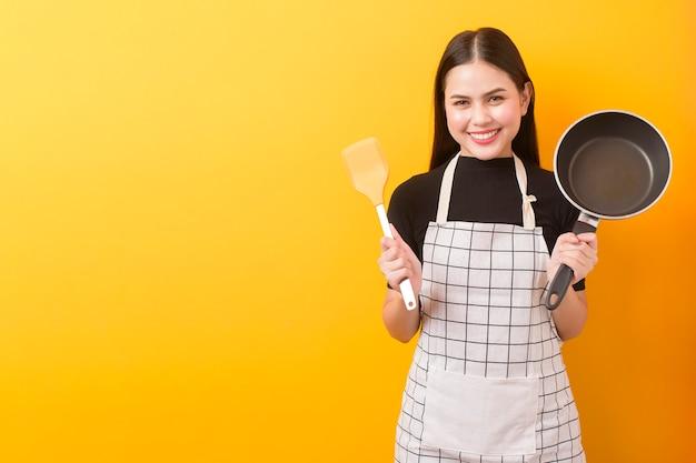 Счастливый женский портрет повара на желтом фоне
