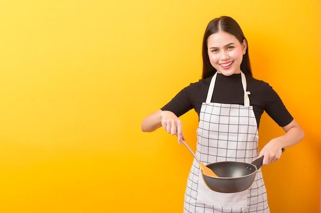 黄色の背景に幸せな女性クックの肖像画