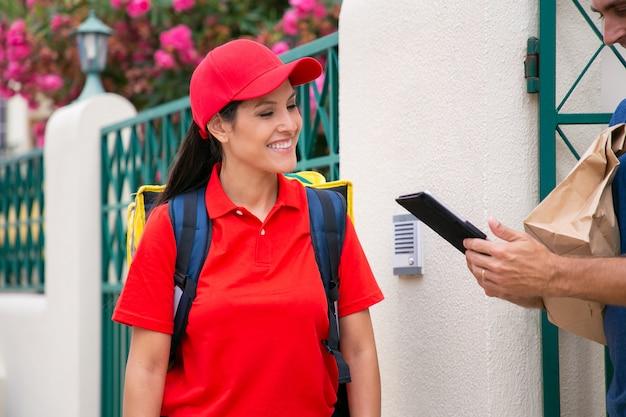 행복 한 여성 택배 주문을 제공 하 고 클라이언트에 웃 고. 라틴 배달원에서 종이 가방을 받고 태블릿을 들고 자른 백인 남자. 음식 배달 서비스 및 포스트 개념