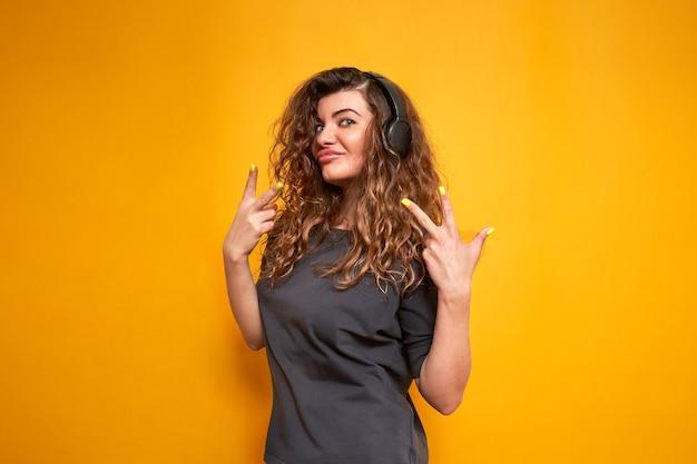 곱슬곱슬한 행복한 여성은 주황색으로 격리된 배경에서 큰 검은색 헤드폰으로 음악을 듣습니다.