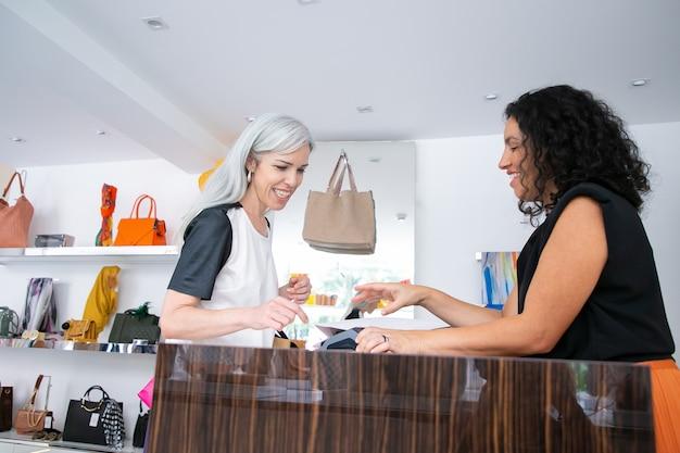계산대에서 구매를 지불하고 계산원과 이야기하고 pos 단말기와 신용 카드를 사용하는 행복한 여성 고객. 측면보기. 쇼핑 및 서비스 개념