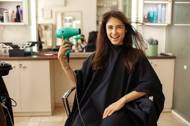 Happy female customer using hairdryer in hairdressing salon.woman sitting in chair in hairsalon. beauty and fashion business, professional service