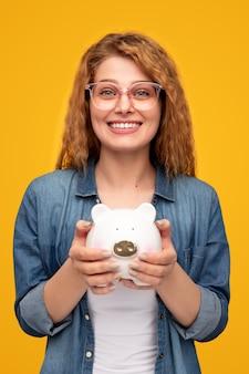 貯金箱を示す幸せな女性