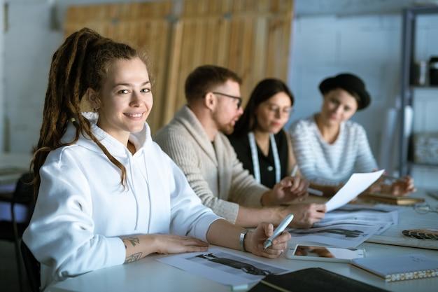 Счастливый женский дизайнер рисует эскиз моды на фоне коллег, работающих с бумагами