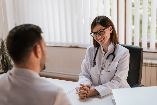 Happy female doctor discussing with patient at table in clinic