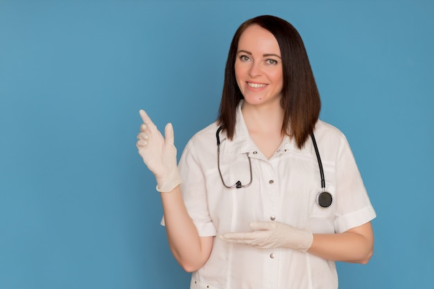 Happy female doctor in medical gloves with a stethoscope pointing to copy space