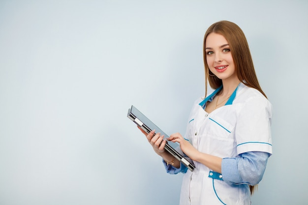 Happy female doctor using tablet computer isolated on a white background. beautiful girl in a white coat