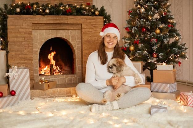 幸せな女性はセーターと赤い帽子を着て、かわいい犬を抱き、ライトでクリスマスツリーを楽しんで、雰囲気のある感情的な瞬間、カメラを直接見ている足を組んで笑顔の女性。