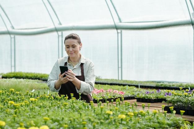 스마트폰으로 온라인 원예 비디오를 보고 있는 행복한 여성 농부