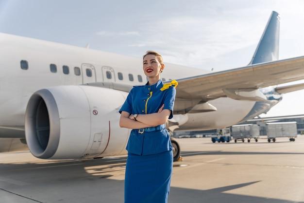 Счастливый женский бортпроводник позирует возле большого самолета