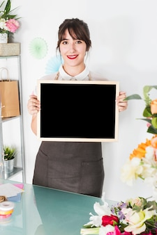 Happy female florist holding blank slate