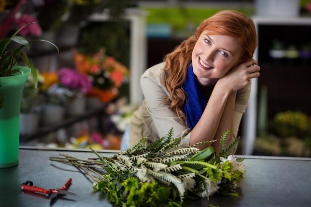 フラワーショップで傾いている幸せな女性花屋