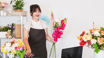 Happy female florist with bunch of flowers