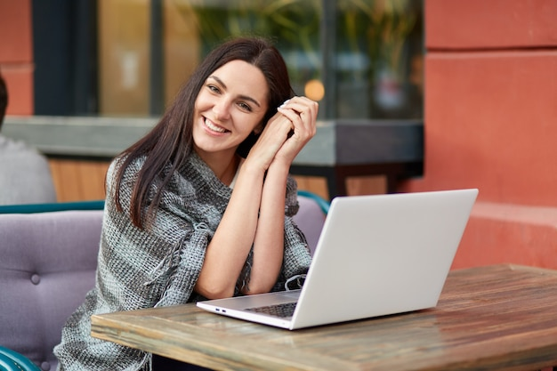 Happy female freelancer satisfied with distance job, works in outdoor restaurant, has coverlet on shoulders, sits in front of opened laptop