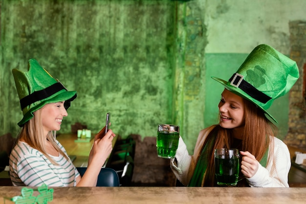 Happy female friends celebrating st. patrick's day together with drinks and smartphone