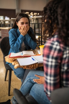 Счастливые подруги вместе делают домашнее задание в кафе