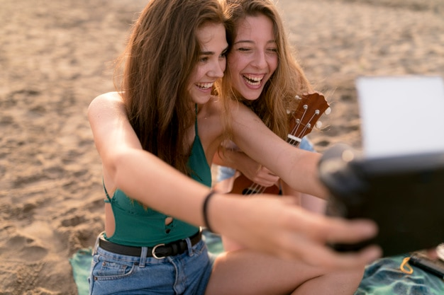 Happy female friends enjoying at beach taking selfie through instant camera