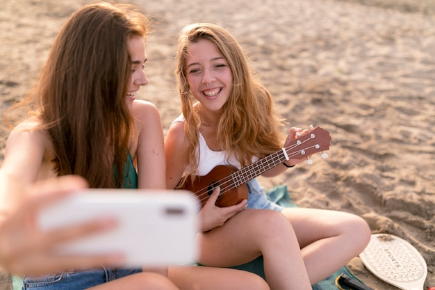 Happy female friends enjoying at beach taking selfie