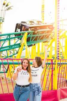 Happy female friends hanging out together in front of roller coaster ride