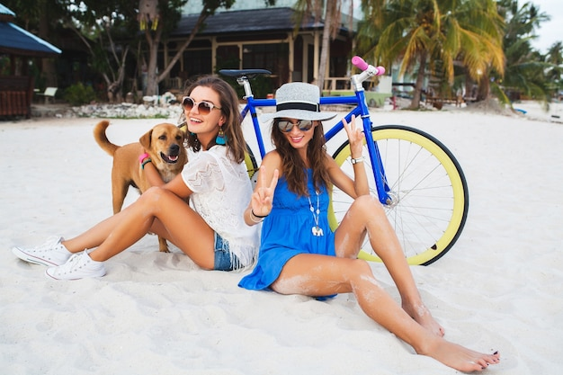 熱帯のビーチで楽しんでいる幸せな女性の友人、自転車でタイの休暇で旅行している女性