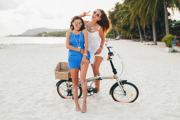 熱帯のビーチで楽しんで幸せな女性の友人