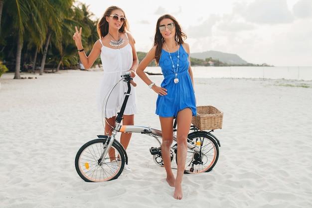 Счастливые подруги веселятся на тропическом пляже