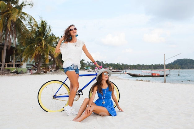 Amici femminili felici divertendosi sulla spiaggia tropicale, donne che viaggiano in vacanza in thailandia con la bicicletta
