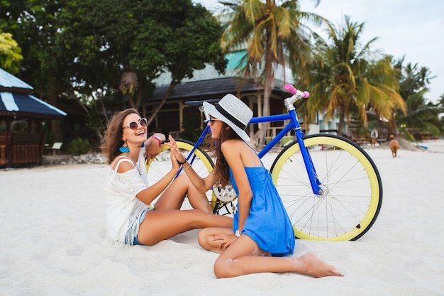Happy female friends having fun on tropical beach, women traveling on vacation in thailand with bicycle
