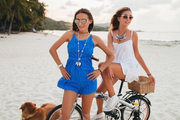 Amici femminili felici divertendosi sulla spiaggia tropicale