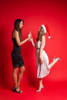 Счастливые подруги в платьях весело проводят время вместе и пьют шампанское, изолированные на красной стене