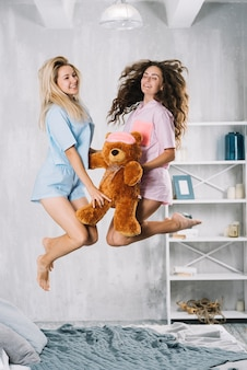 Happy female friends jumping over bed with soft toy