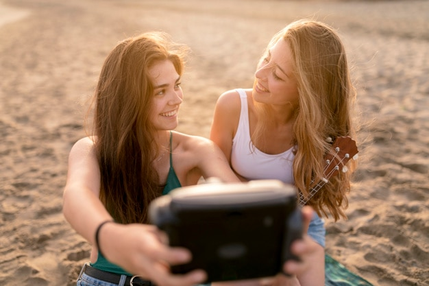 Happy female friends looking at each other taking self portrait at beach