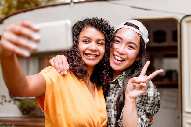 Happy female friends making the peace sign
