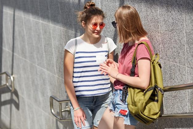 Счастливые подруги встречаются на улице, стоят возле метро, делятся новостями друг с другом, носят модные оттенки, держат рюкзак