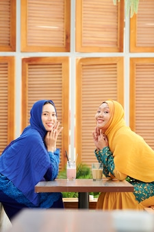 Happy female friends meeting in cafe