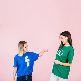Happy female friends pointing at each other on pink background
