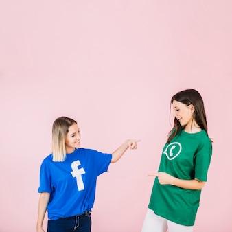 Amici femminili felici che indicano a vicenda su fondo rosa