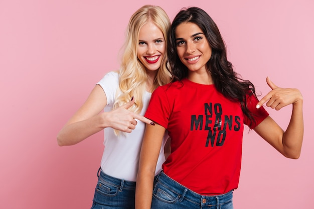 Happy female friends pointing at shirt with phrase and smiling isolated