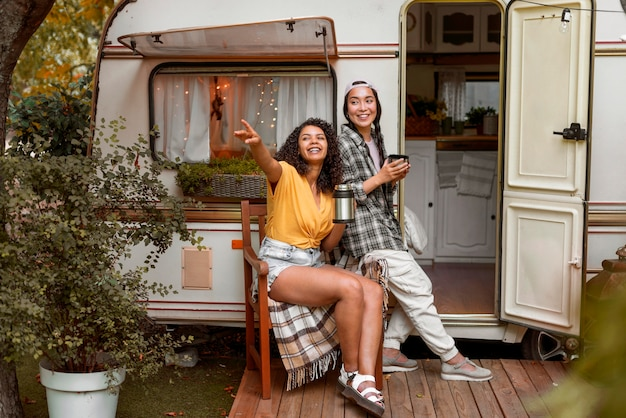 Happy female friends sitting next to a camper van
