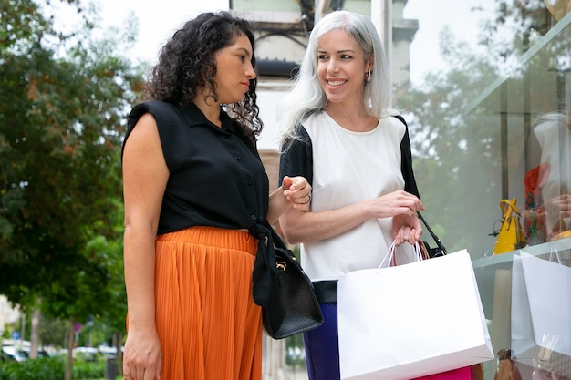 Happy female friends standing at shop window with accessories, holding shopping bags, smiling and chatting. back view. window shopping concept