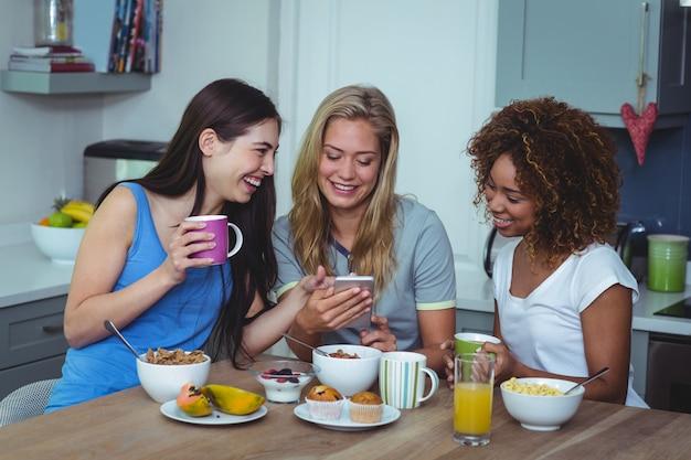 Happy female friends using smartphone