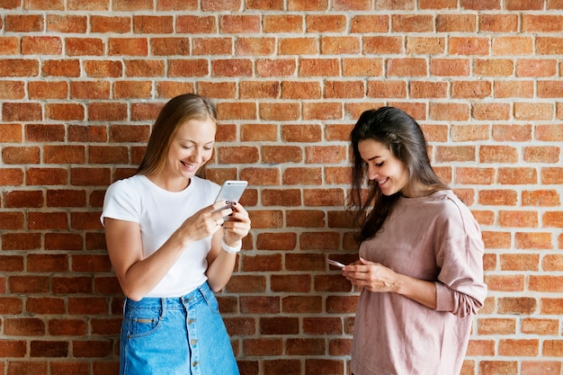 Happy female friends using smartphones