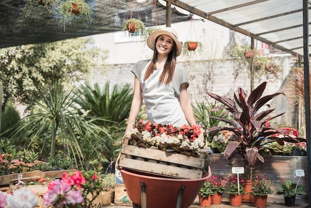Happy female gardener carrying crate of flowers in wheelbarrow