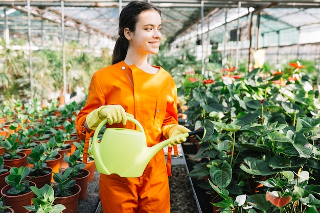 Happy female gardener holding watering can in greenhouse